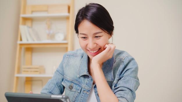 Junge asiatische frau, die unter verwendung der tablette social media überprüfend arbeitet, während sie sich zu hause auf schreibtisch im wohnzimmer entspannen. zeit zu hause konzept genießen.