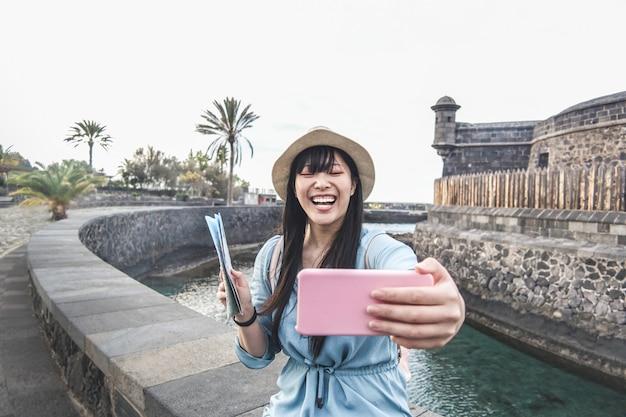 Junge asiatische frau, die video für vlog mit smartphone-kamera macht