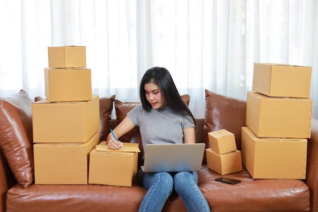 Junge asiatische frau, die von zu hause aus mit smartphone und online-einkaufs-bestellbox überprüft und arbeitet