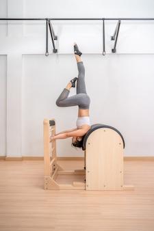 Junge asiatische frau, die während ihres gesundheitstrainings an einer pilates-leiter-fassmaschine arbeitet