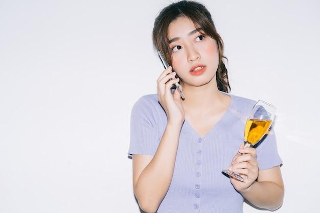 Junge asiatische frau, die wein trinkt und smartphone auf weiß verwendet