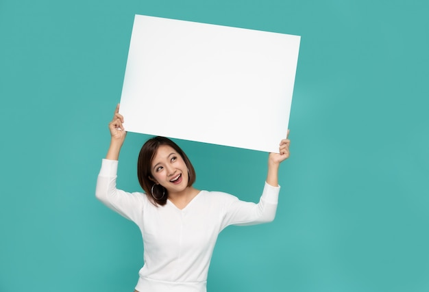 Junge asiatische frau, die weißes großes papier hält und betrachtet.