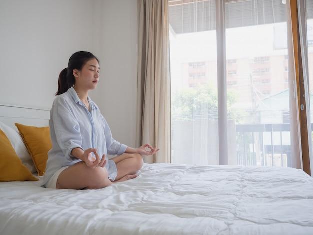 Junge asiatische frau, die yoga auf bett tuend sitzt und übt