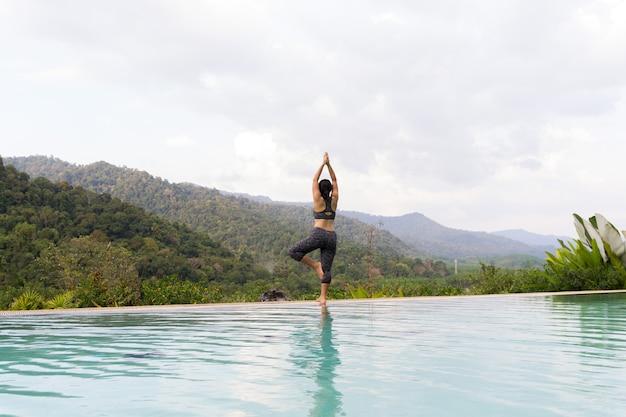Junge asiatische frau, die yogaübung im freien nahe schwimmbad tut