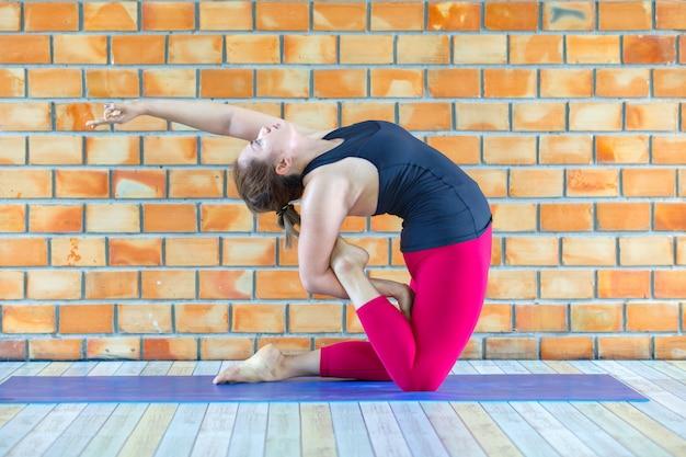 Junge asiatische frau, die yogaübung im studio tut