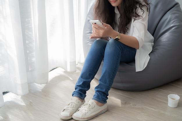 Junge asiatische frau, die zu hause mobile im wohnzimmer verwendet