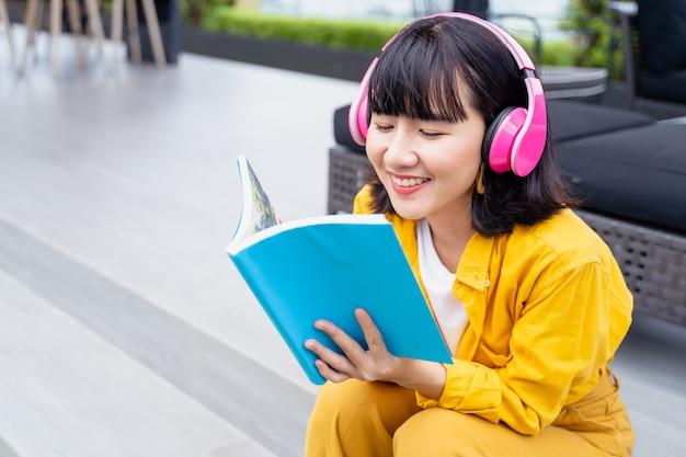 Junge asiatische frau, die zu hause musik von den kopfhörern liest und hört