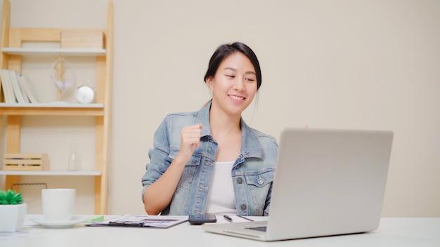 Junge asiatische frau, die zu hause unter verwendung des laptops auf schreibtisch im wohnzimmer arbeitet. asien-geschäftsfrauerfolgsfeier, die glückliches büro zu hause tanzen fühlt.