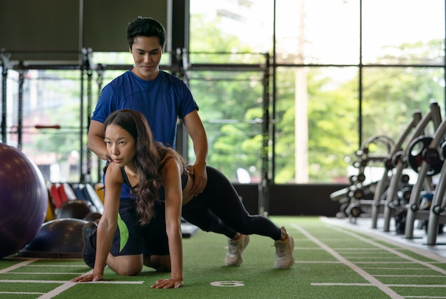 Junge asiatische frau drücken übung mit persönlichem trainer am turnhallensportverein hoch