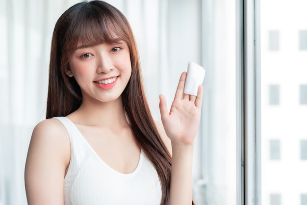 Junge asiatische frau entfernte make-up am fenster