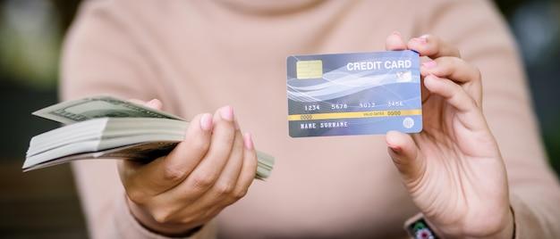 Junge asiatische frau entscheidet zwischen dem zahlen mit kreditkarte oder bargeld in der kaffeestube