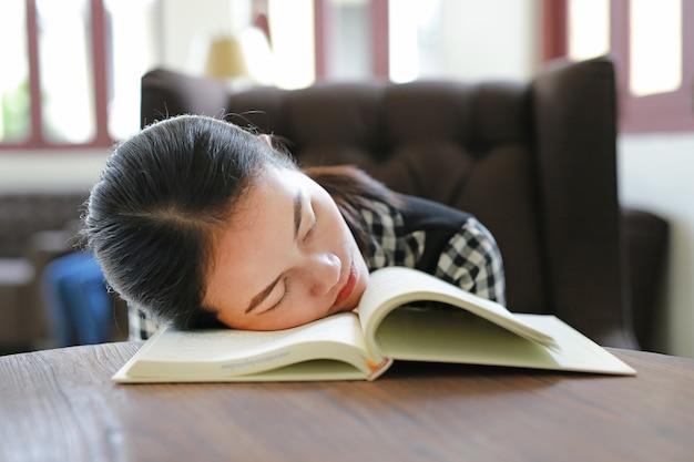 Junge asiatische frau entspannen sich und schlafen in der bibliothek.