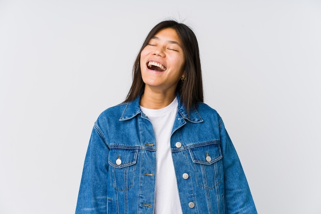 Junge asiatische frau entspannte sich und glückliches lachen, der ausgedehnte hals, der zähne zeigt.