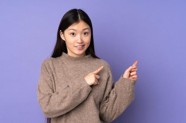 Junge asiatische frau erschrocken und zur seite zeigend