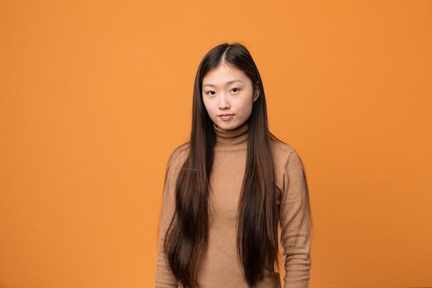 Junge asiatische frau gegen einen orange hintergrund