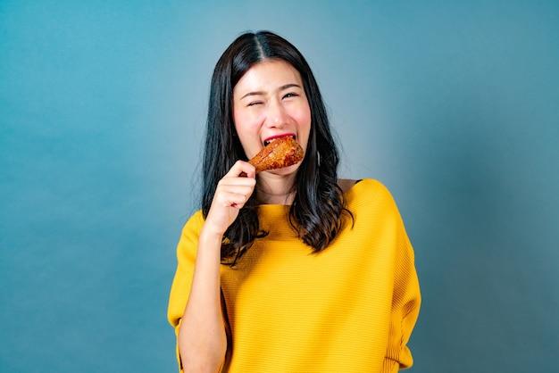 Junge asiatische frau genießen gebratenes hühnertrommelstock essen