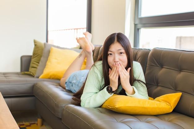 Junge asiatische frau glücklich und aufgeregt, überrascht und erstaunt, mund mit händen bedeckend, mit einem niedlichen ausdruck kichernd