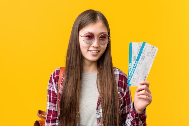 Junge asiatische frau, halten flugtickets lächelnd überzeugt mit den gekreuzten armen.