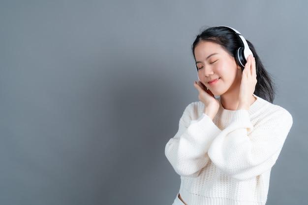 Junge asiatische frau hört und genießt musik mit kopfhörern auf grauem hintergrund