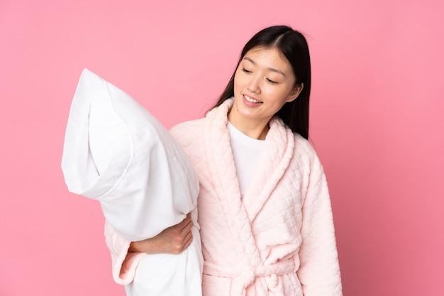 Junge asiatische frau im pyjama auf rosa wand mit glücklichem ausdruck