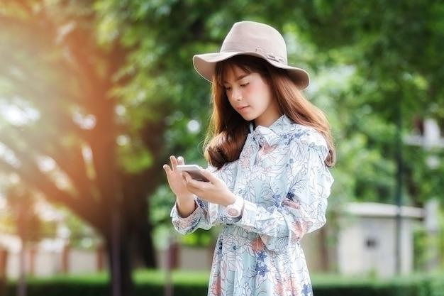Junge asiatische frau im retrostil mit mobiltelefon im park