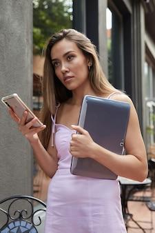 Junge asiatische frau im rosa kleid, die draußen mit laptop mit smartphone steht