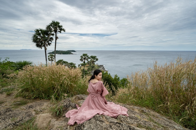 Junge asiatische frau im rosa kleid genießen und entspannen sich am standpunkt promthep cape landmark in phuket