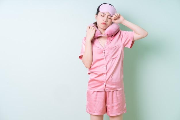 Junge asiatische frau im schlafanzug auf grünem hintergrund