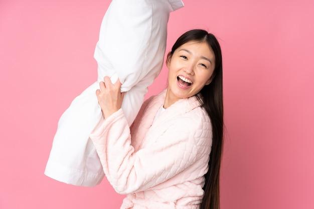Junge asiatische frau im schlafanzug lokalisiert auf rosa wand
