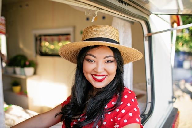 Junge asiatische frau im strohhut, die lächelt und aus dem fenster des wohnmobils späht