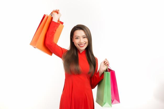 Junge asiatische frau im traditionellen ao dai kleid einkaufen, hand hält papiertüte, feiert lunar new year oder frühlingsfest