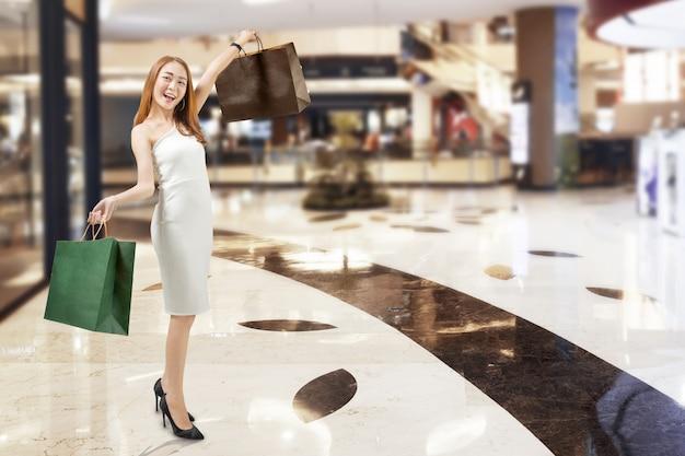 Junge asiatische frau im weißen kleid im einkaufszentrum einkaufen