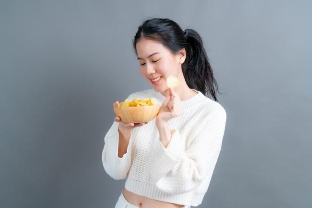 Junge asiatische frau im weißen pullover isst kartoffelchips auf grauem hintergrund