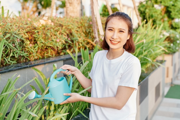 Junge asiatische frau im weißen t-shirt, die pflanzen in ihrem garten gießt.