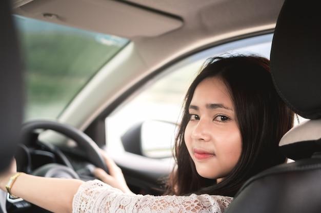 Junge asiatische frau in der freizeitkleidung halten lenkrad und betrachten passagiere