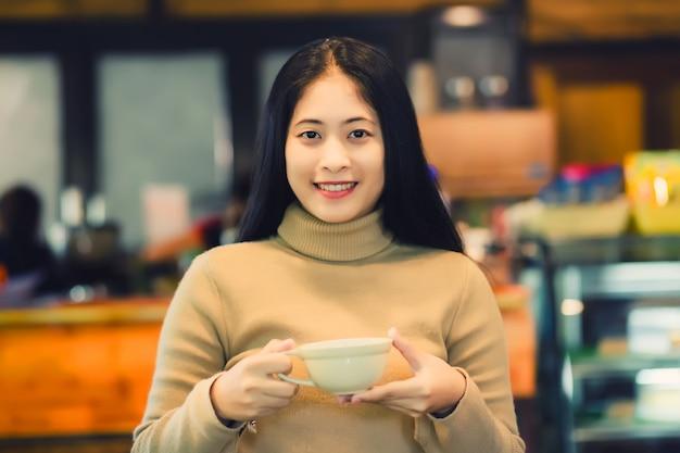 Junge asiatische frau in der kaffeestube