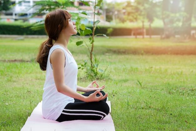 Junge asiatische frau in der meditierenden sportkleidung beim sitzen in der lotoshaltung auf yogamatte