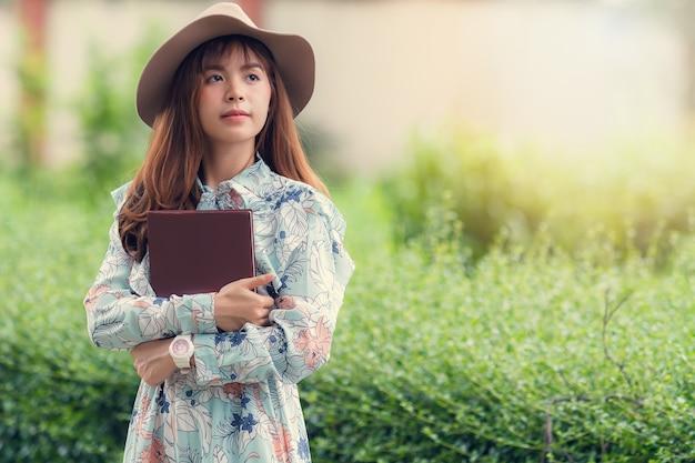 Junge asiatische frau in der retro- art mit einem buch, das in park schlendert