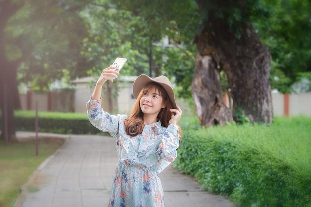 Junge asiatische frau in der retro- art nehmen ein selfie im park