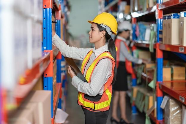 Junge asiatische frau in der sicherheitsweste und im helm, die produkte im lagerregal überprüfen