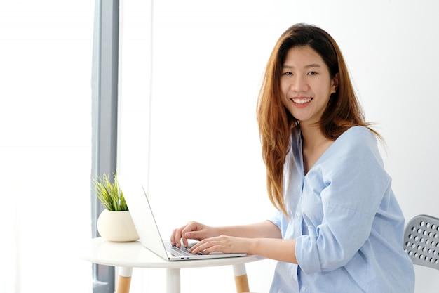 Junge asiatische frau in der zufälligen art unter verwendung des bürohintergrundes der laptop-computers zu hause