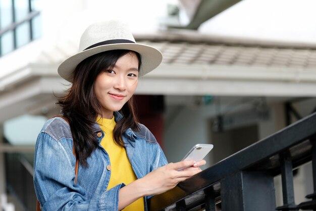 Junge asiatische frau in der zufälligen art unter verwendung des smartphone