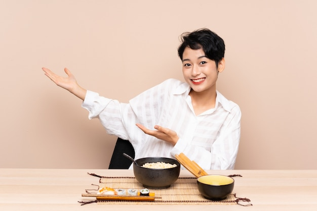 Junge asiatische frau in einem tisch mit schüssel nudeln und sushi, die hände zur seite ausdehnen, um einzuladen, zu kommen