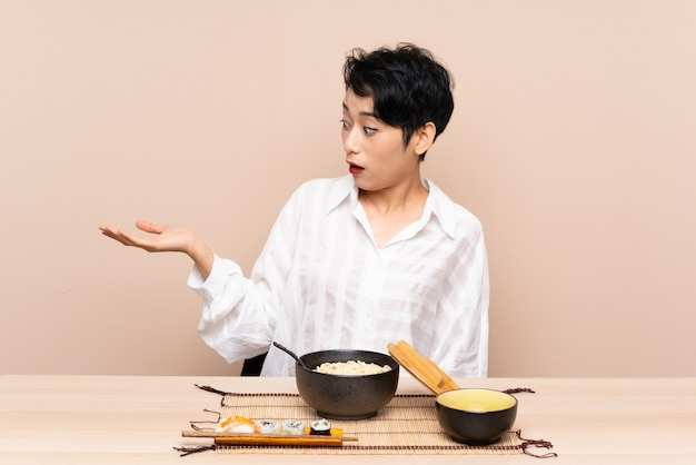 Junge asiatische frau in einem tisch mit schüssel nudeln und sushi halten copyspace imaginär auf der handfläche