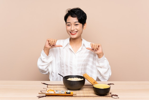 Junge asiatische frau in einem tisch mit schüssel nudeln und sushi stolz und selbstzufrieden