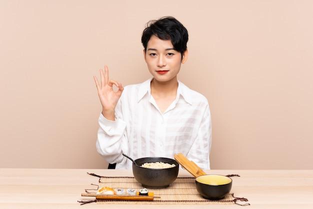 Junge asiatische frau in einer tabelle mit schüssel nudeln und sushi, die ein ok zeichen mit den fingern zeigt