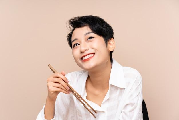 Junge asiatische frau in einer tabelle mit schüssel nudeln und sushi