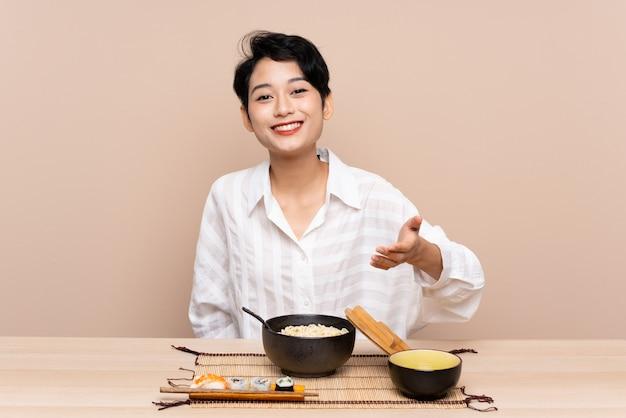 Junge asiatische frau in einer tabelle mit schüssel nudeln und sushihändeschütteln nach viel
