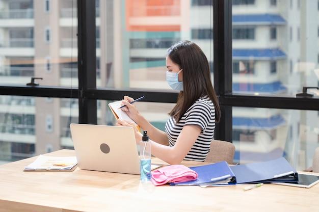 Junge asiatische frau in lässig mit gesichtsmaske und notiz des zeitplans auf dem kalender am neuen normalen büro