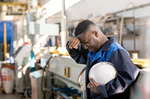Junge asiatische frau in orangefarbenem bauarbeiterhelm mit schutzhandschuhen bei der vorbereitung auf metallarbeiten im fabrikladen